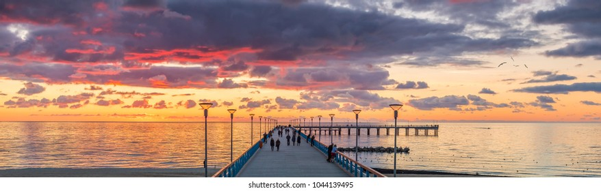 Palanga, Lithuania - October 03, 2013: Colorful sunset at a famous marine pier in the Baltic resort city of Palanga, people are walking and resting