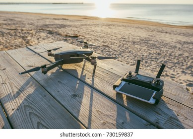 PALANGA, LITHUANIA - SEPTEMBER 27, 2017: Drone DJI Mavic Pro and remote controller with Apple iPhone placed on wood table, sea and beach in background