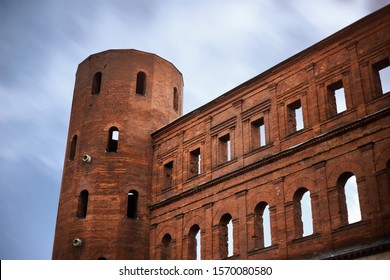Palatine Gate (In Italian: Porta Palatina) also known as Doranea or Doranica (since it led to the Dora river). Roman Age city gate located in Turin, nearby open market. Facade Close Up. Long Exposure