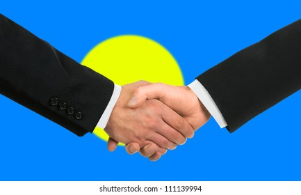 The Palau flag and business handshake