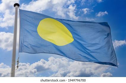 Palau flag, Republic of Palau national symbol on a flagpole waving against blue cloudy sky