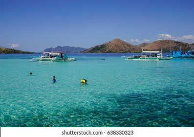 Palawan, Philippines - Apr 11, 2017. Many people swimming on the sea under blue sky in Palawan, Philippines. The Palawan coast is one of the most unspoilt places in the world.
