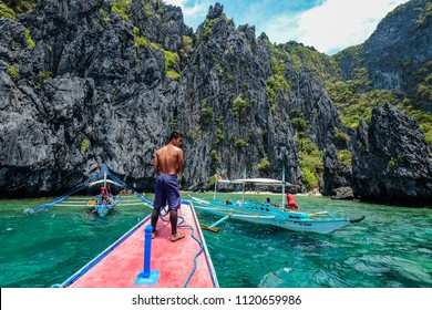 Palawan, Philippines - Apr 5, 2017. A man standing on tourist boat in Palawan, Philippines. Palawan is the island of idyllic tropical beauty.
