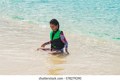 PALAWAN, PHILIPPINES - JANUARY 13, 2017 -  young girl on the white sands of the tropics, with ocean and blue sky in the background