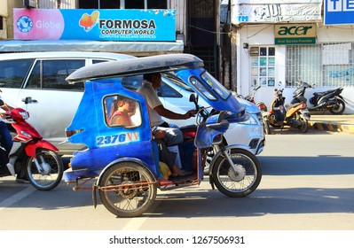 Palawan, Philippines - September 26, 2018: Tricycle motorbike taxi on city street with passengers. Motor tricycle are the both cheap common means transportation and symbol of Philippine culture