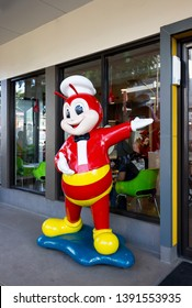 Palawan, Philippines - September 27, 2018: Jollibee fast food restaurant with mascot at entrance is a smiling giant red bee. The most popular fried chicken and fast foods franchise in Philippines