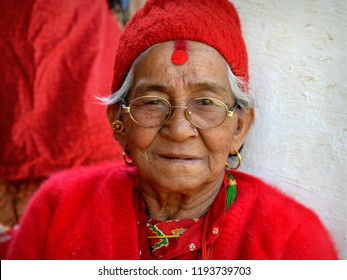 PALCHOWK, HELAMBU / NEPAL - MAY 11, 2018: Old Nepali Chhetri woman with a large red bindi and red sindoor on her forehead poses in her all-red clothing for the camera, on May 11, 2018.