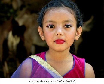 PALCHOWK, HELAMBU REGION / NEPAL - MAY 11, 2018: Dressed-up little Nepali Chhetri girl with make-up poses for the camera during a traditional Chhetri village wedding, on May 11, 2018.