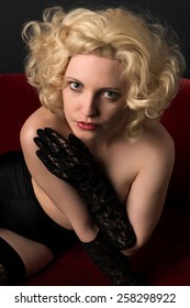 Pale blonde on a red couch topless in black