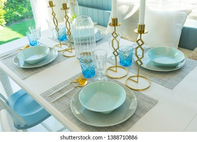 Pale blue plate setting on table with gold candle holder in home dining room interior.