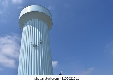 Pale blue water tower in Dacono, CO, with sunny blue sky and some clouds; view from base, left frame