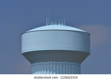 Pale blue water tower in Dacono, CO, with sunny blue sky and some clouds; distance shot, close up of tank