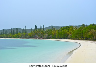 The pale blue waters of a tropical beach lap onto golden sand. Green trees grow on the edge of the sand and surround a wooden villa. Hills are in the distance, and the sky is clear.