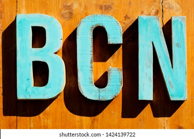 pale blue wooden three-dimensional letters forming the text BCN, an abbreviation for Barcelona, Spain, on a wooden background