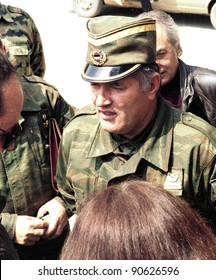 PALE, BOSNIA - APR 11: Reporters cluster around Bosnian Serb general Ratko Mladic as he speaks before attending church services in Pale, Bosnia, on Sunday, April 11, 1993.