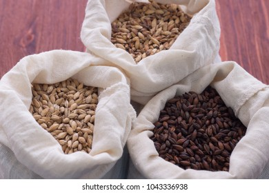 Pale, caramel, chocolate malt in a bags. Craft beer brewing from grain barley malt in process. Ale or lager from pale or dark pilsner malt. wooden background