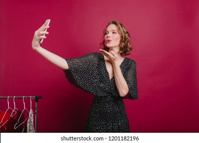 Pale cute woman sending air kiss while posing in dressing room. Charming short-haired girl in vitage dress making selfie standing next to hangers with clothes.