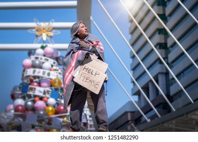 Pale exhausted Asian homeless walking in the modern city against christmas tree, homeless and hungry holding his bag and cardboard pape, Homeless concept