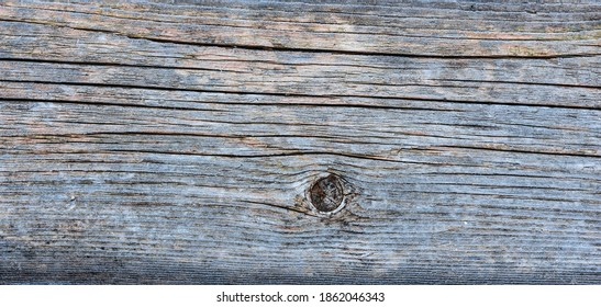 Pale faded brown and cool blue reclaimed pine wood surface with aged boards lined up. Weathered wooden planks on a wall or floor texture. Neutral stained vintage wood background.