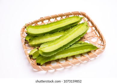 Pale green winged bean pods on a bamboo sieve