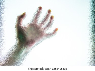 a pale, human hand is behind a pane of glass