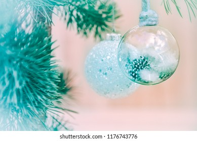 Pale pastel white turquoise to Tiffany blue green fluffy feather and glass shards Christmas decoration baubles on mauve pink background. Happy holidays and New Year season greetings card wallpaper.