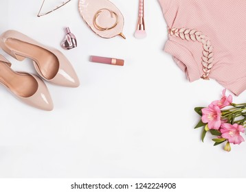 Pale pink feminine accessories and flowers on the white background. Stylish flat lay.