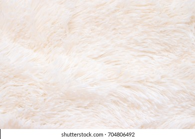 Pale pink shaggy blanket texture as background. Fluffy fake textile fur.