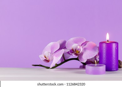 Pale purple orchid on a white table with purple background. Scented candles on the table one of the two ignited