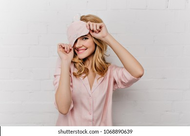 Pale smiling girl with curly hair playfully posing on white background. Chilling woman in eyemask and silk pajama laughing at home.