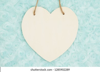 Pale teal rose plush fabric background with wood hanging heart to provide copy-space for your message