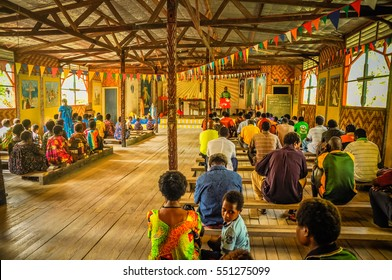 Palembe, Papua New Guinea - July 2015: Photo of native people sitting on wooden benches during mass in wooden church in Palembe, Sepik river in Papua New Guinea. Documentary editorial.