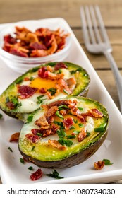 Paleo breakfast of baked avocado egg boats with bacon crumbles and chives on white rectangle plate with whole wheat toast