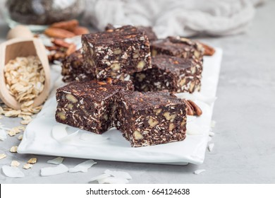 Paleo chocolate energy bars with rolled oats, pecan nuts, dates, chia seeds and coconut flakes, horizontal, copy space