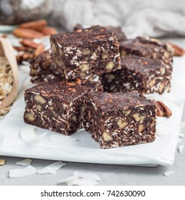 Paleo chocolate energy bars with rolled oats, pecan nuts, dates, chia seeds and coconut flakes, square format
