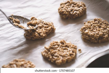 paleo dessert, homemade cookies made of oatmeal and banana . Low carb diet recipes. less sugar consumption. spoon and raw dough on baking sheet.