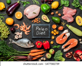Paleo diet concept. Raw ingredients for Paleo diet - fish, seafood, poultry meat, vegetables and fruits and words Paleo Diet on dark background. Top view or flat lay.
