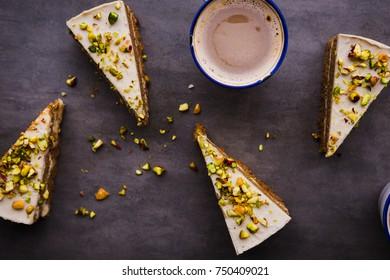 Paleo raw vegan pistachio carrot cake with cashew cream layers. Dark food photography concept