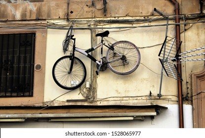 Palermo, Italy - October 16, 2016: funny image of a mountain bike bicycle hanging on a street wall