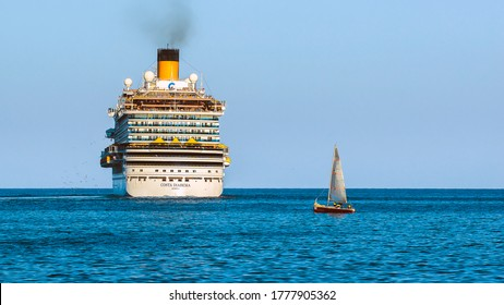 Palermo, Italy. October 26, 2018. Illuminated by the setting sun, a large white cruise ship floating away and a small gray yacht passing by against the backdrop of blue sky and blue sea.