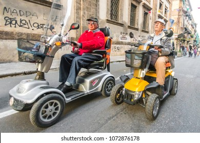 Palermo, Italy, October 31, 2017: Older men on electric scooters for disabled people ride along the street