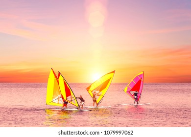 Palermo, Italy, October 31, 2017: Group of windsurfers catch wind in the sea at sunset