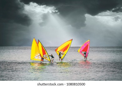 Palermo, Italy, October 31, 2017: Group of windsurfers catch wind in the sea in a storm