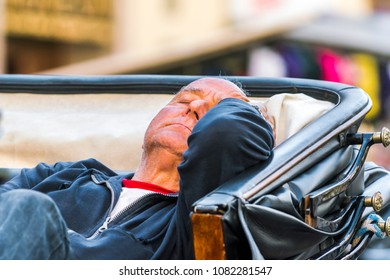 Palermo, Italy, October 31, 2017: An elderly coachman is sleeping in a carriage