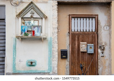 Palermo, Italy, September 19, 2019: Detail of a facade of a house with a wooden door and a small altar with images of the Virgin Mary and Catholic cross. Travel concept