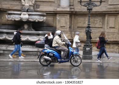 PALERMO, SICILY - NOV 28, 2018 - Motorcycle on rain slick street in Palermo, Sicily, Italy