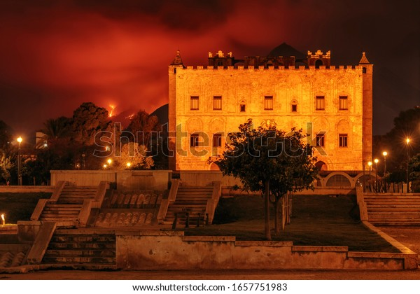 Palermo, Sicily/Italy - February 26 2020: Zisa Castle with Forest and Bush Fire in the Background at night
