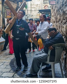 Palestinian man sleeping near a religious tourist group which walking the same way of Jesus to his crucifixion in Via Dolorosa ( way of sorrow ) in jerusalem in israel ( Palestine) 24 october 2018
