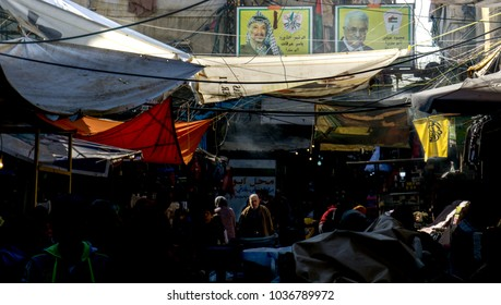 Palestinians walking in the shatila market under the poster of Yasser Arafat and mahmoud abbas in Sabra and shatila refugee camp in beirut Lebanon 3 February 2018