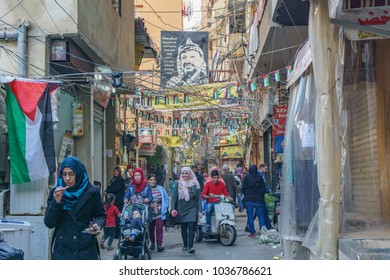 Palestinians walking under the poster of Yasser Arafat in Sabra and shatila refugee camp in beirut Lebanon 3 February 2018